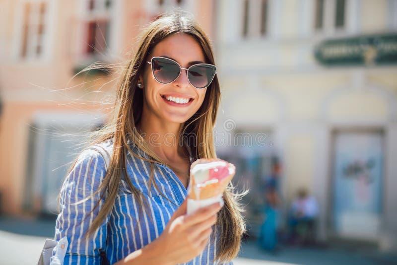 Junge gl?ckliche Frau, welche die Eiscreme, im Freien isst stockfoto