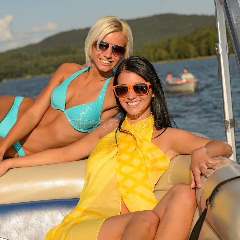 Junge lächelnde Frauen, die auf Boot ein Sonnenbad nehmen lizenzfreies stockfoto