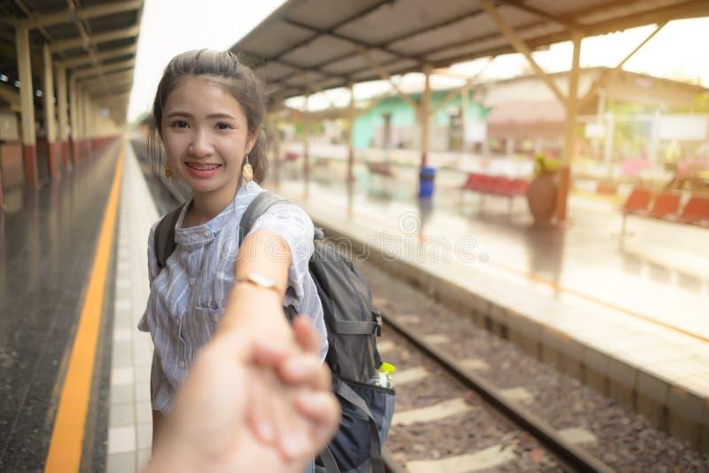Junge gl?ckliche Frauenholding-Mannhand, die am Bahnhof f?hrt Paare in der Liebe am Feiertag lizenzfreie stockfotos