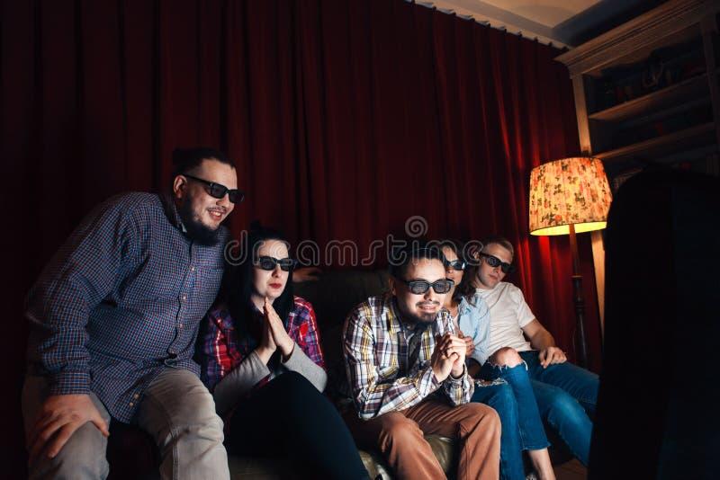 Junge glückliche Freunde in den Gläsern 3d sehen zu Hause fern stockbild
