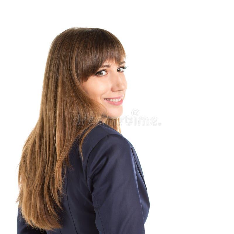 Junge glückliche Geschäftsfrau, die über Schulter flüchtig blickt stockfotografie