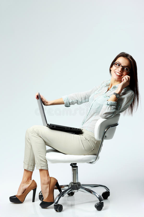 Junge glückliche Geschäftsfrau, die auf dem Stuhl mit Laptop sitzt stockfotos