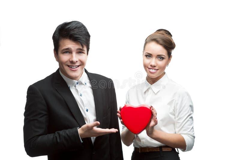 Junge glückliche Geschäftsleute, die roten Valentinsgruß anhalten lizenzfreies stockfoto