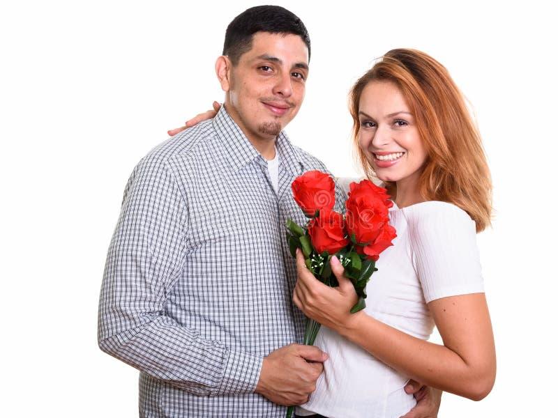 Junge glückliche hispanische Paare, die und in der Liebe hält rote Rosen lächeln lizenzfreies stockfoto