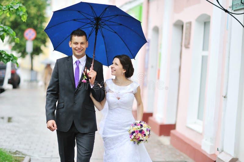 Junge glückliche Hochzeitspaare, die durch den Regen in einer alten Stadt gehen stockbild
