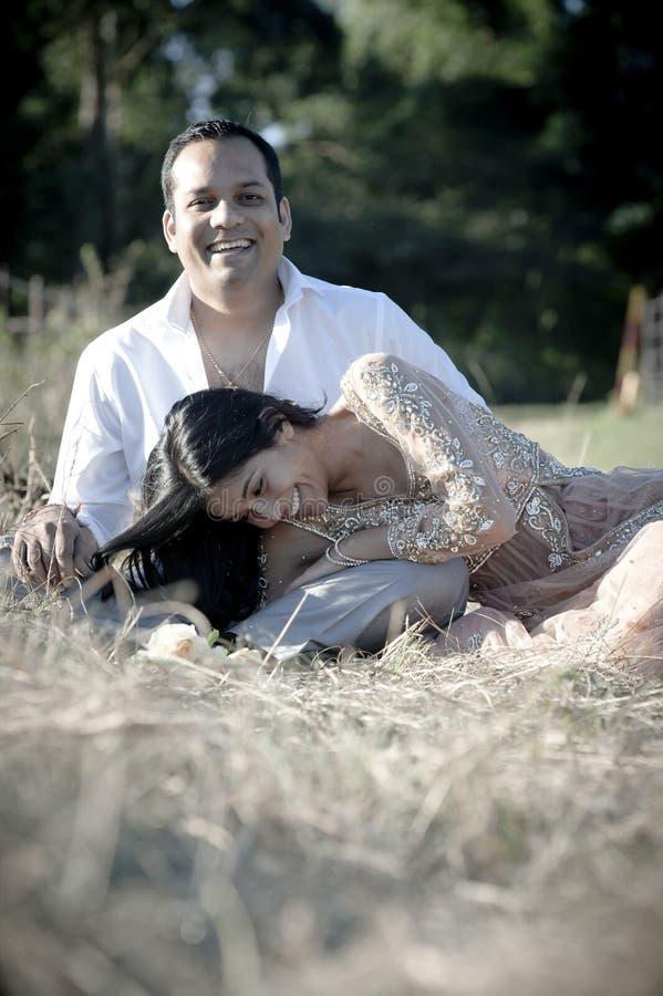 Junge glückliche indische Paare, die auf dem Gebiet lachen stockbild