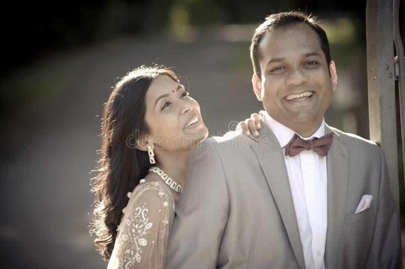 Junge glückliche indische Paare, die draußen im Sonnenschein lachen stockfoto