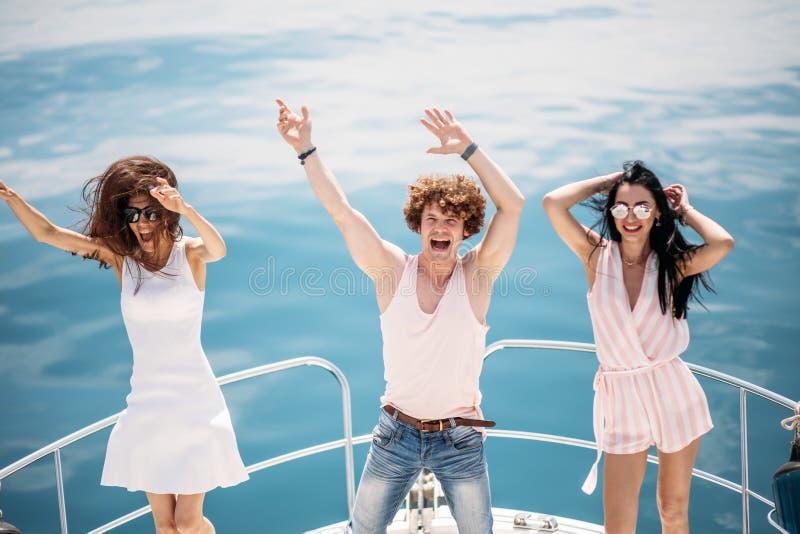 Junge glückliche kaukasische Leute, die in Bootspartei tanzen lizenzfreies stockfoto
