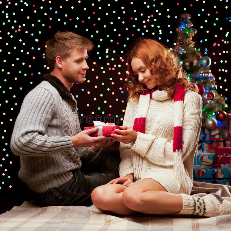 Junge glückliche lächelnde beiläufige Paare, die ein Geschenk bilden stockfotografie