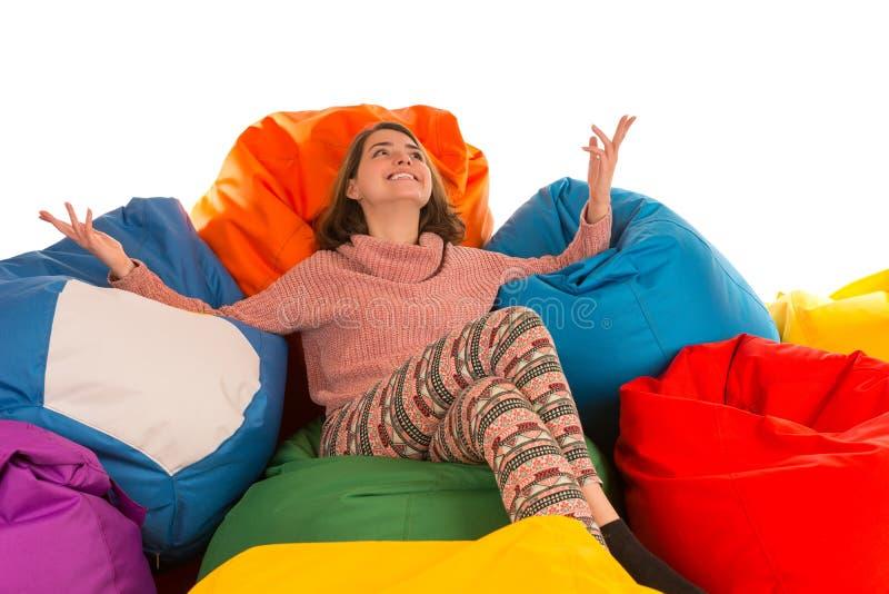 Junge glückliche lächelnde Frau, die zwischen Sitzsackstühlen sitzt stockfoto