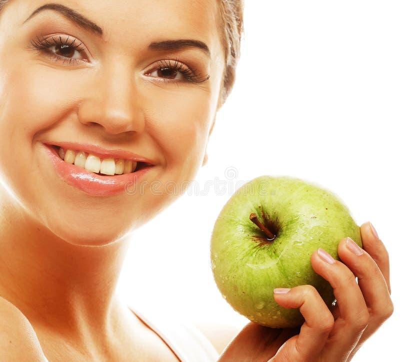 Junge glückliche lächelnde Frau mit grünem Apfel lizenzfreie stockfotografie