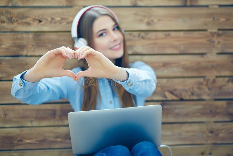 Junge glückliche lächelnde Frau mit Kopfhörern macht Herzform mit den Händen, die auf dem Hintergrund der Wand von hölzernem sitz stockbild