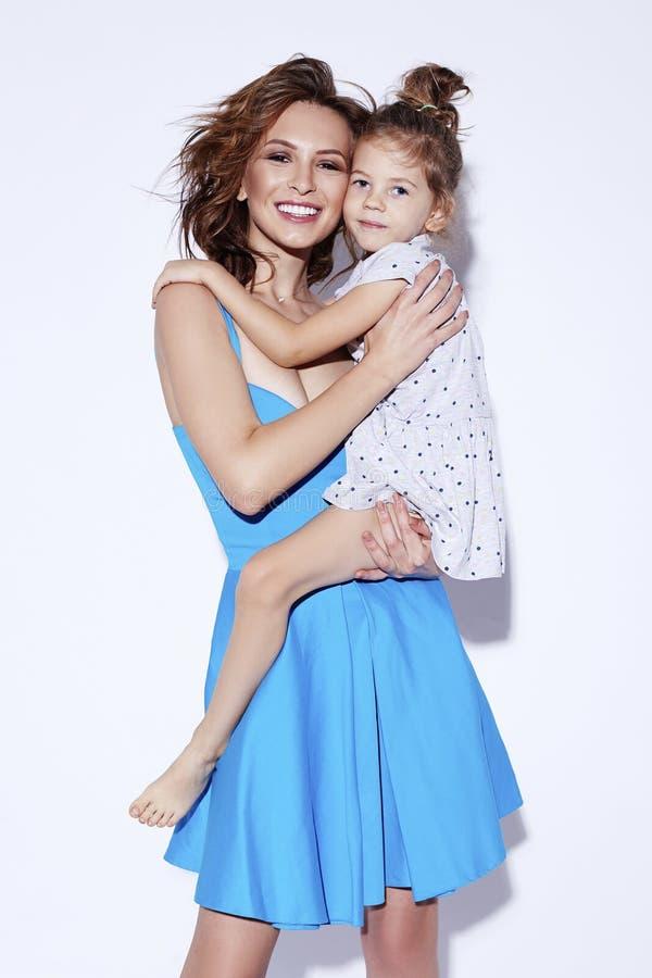 Junge glückliche lächelnde nette Mutter, die ihre entzückende kleine Tochter betrachtet Kamera hält Muttertag marschieren Konzept lizenzfreies stockbild