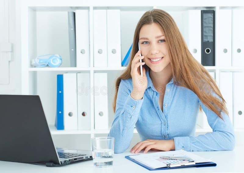 Junge glückliche langhaarige Geschäftsfrau, die am Telefon spricht und Anmerkungen in Büro schreibt stockfotografie