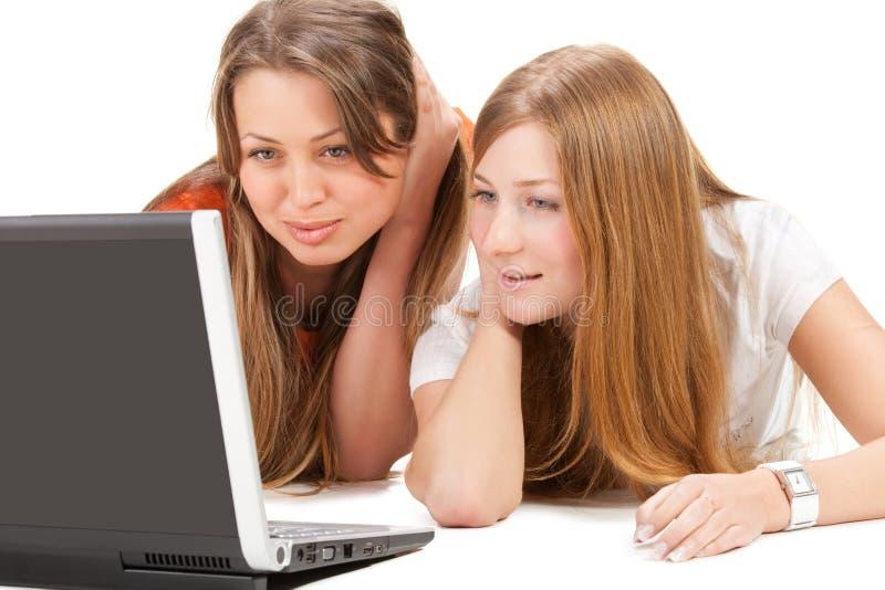 Junge glückliche Mädchenarbeit des Kursteilnehmers zwei über Laptop lizenzfreies stockbild