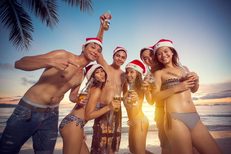 Junge glückliche Menschen auf dem Strand, der Weihnachtsfest hat lizenzfreies stockbild