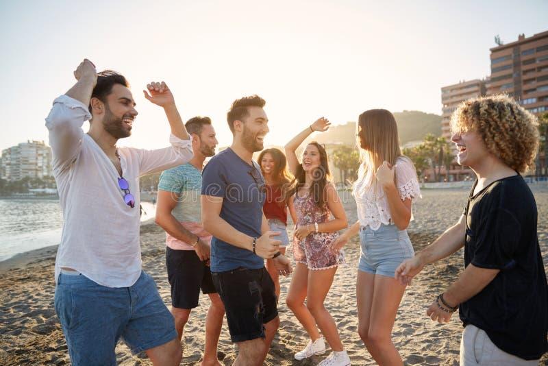 Junge glückliche Menschen, die auf Strand partying sind stockfoto