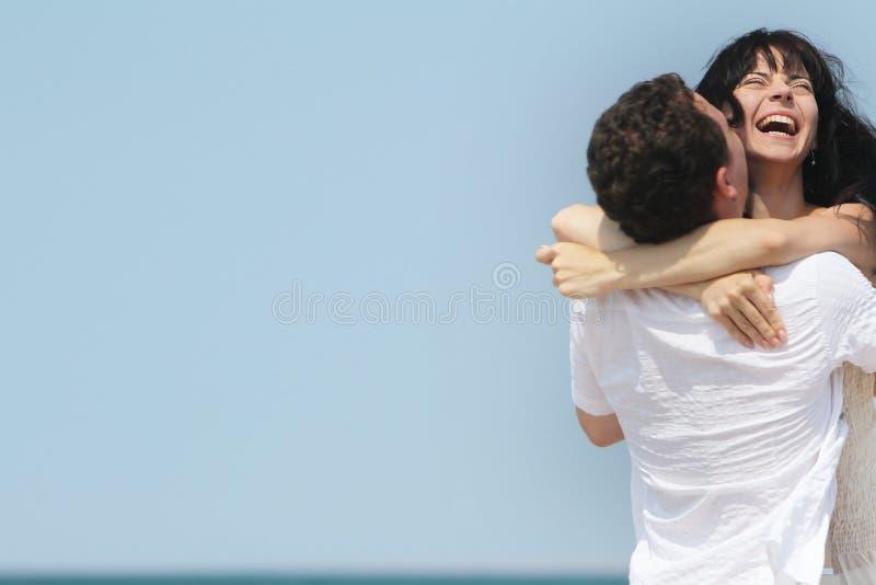 Junge glückliche Paare über Himmelhintergrund lizenzfreies stockfoto