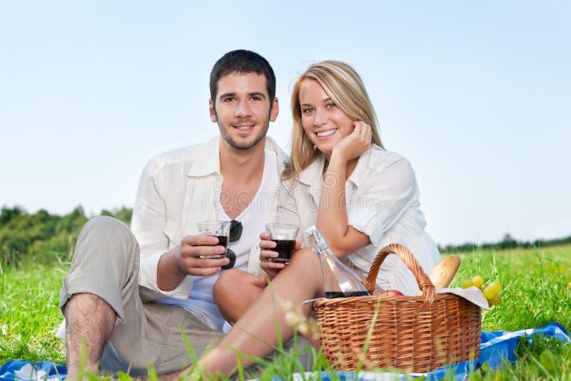 Junge glückliche Paare des Picknicks, die mit Wein feiern lizenzfreie stockbilder