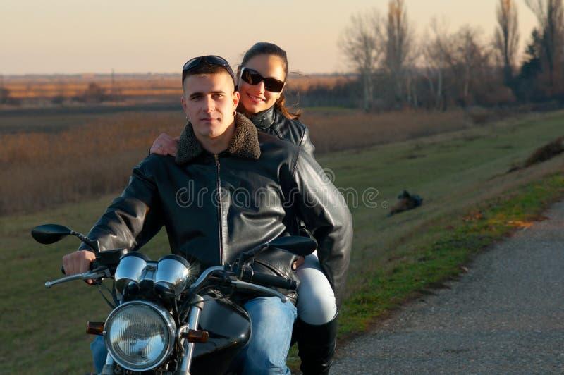 Junge glückliche Paare, die ein Motorrad reiten stockbild
