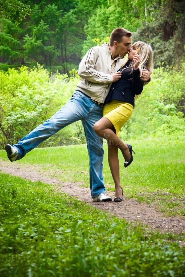 Junge glückliche Paare, die in einem Park küssen stockfotos