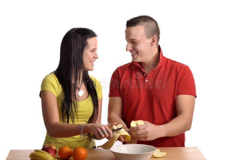 Junge glückliche Paare, die einen Fruchtsalat zubereiten lizenzfreies stockbild