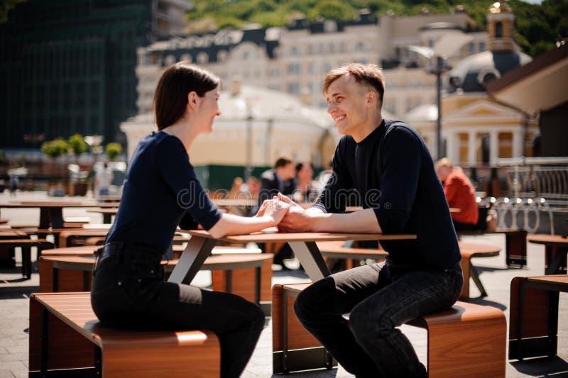 Junge, glückliche Paare, die Hände über der Tabelle an einer Gaststätte lächeln und anhalten lizenzfreies stockfoto