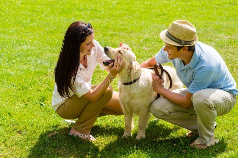 Junge glückliche Paare, die mit Labrador-Hund spielen stockbilder