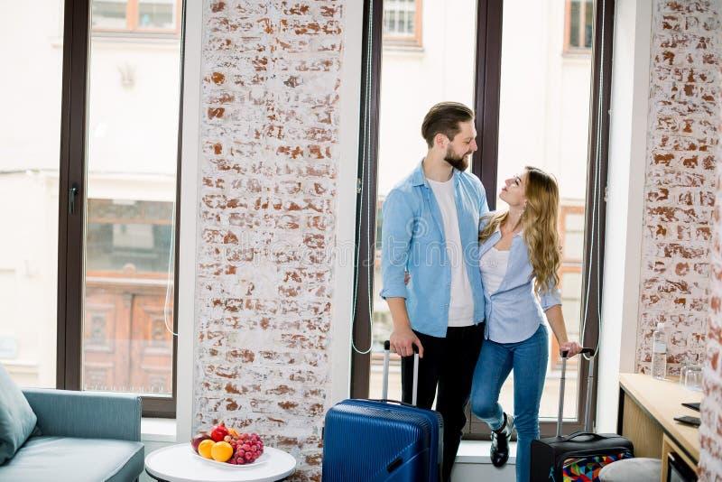 Junge glückliche Paare, Mann und Frau, die im Hotelzimmer ankommen, vor dem Fenster stehen, umherziehen und lizenzfreies stockbild