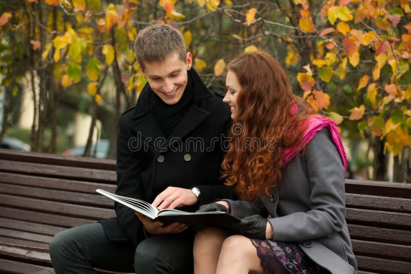 Junge glückliche Paare mit Buch auf der Bank lizenzfreie stockfotos