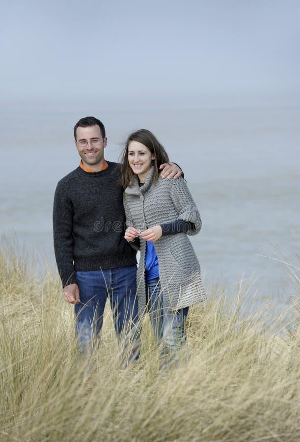 Junge glückliche Paare am Strand stockbild