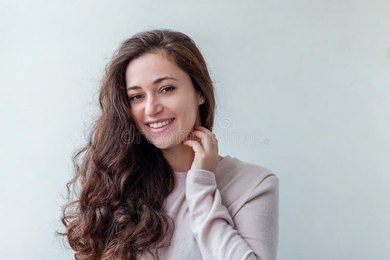 Junge glückliche positive brunette Frau des Schönheitsporträts auf weißem Hintergrund stockfoto