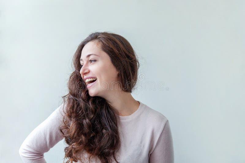 Junge glückliche positive brunette Frau des Schönheitsporträts auf weißem Hintergrund stockbilder