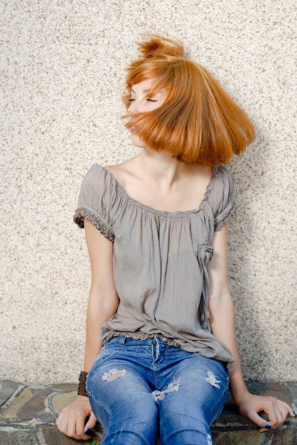 Junge glückliche Redhead-Jugendliche, die mit dem Haar spielt stockbild