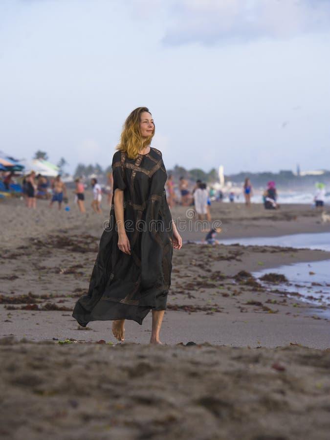 Junge glückliche schöne und bezaubernde blonde Frau, die als Berufsmodell am Strand trägt das stilvolle Kleid betrachtet das Meer stockfoto