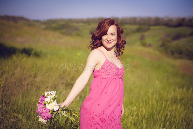 Junge glückliche schwangere Frau, die das Leben in der Natur sich entspannt und genießt stockfoto