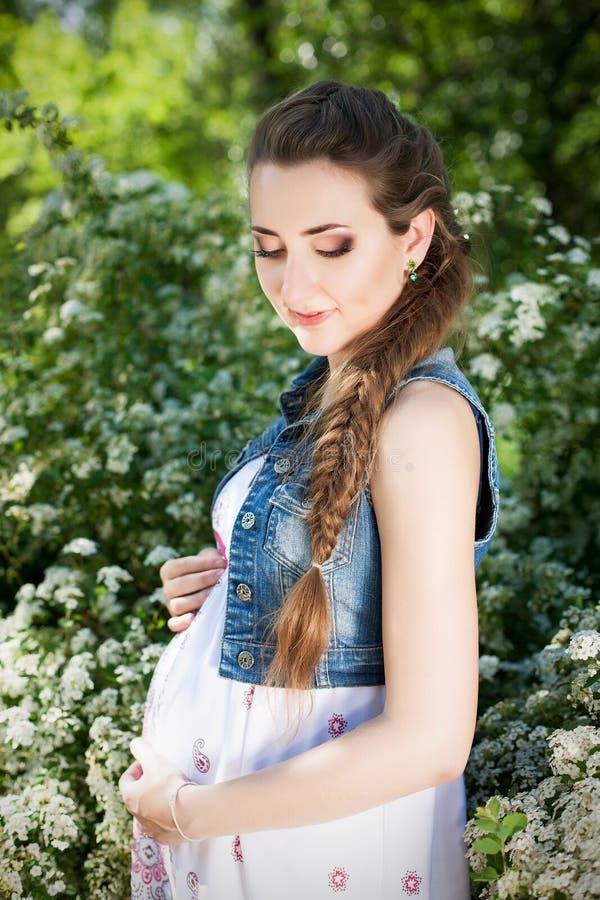 Junge glückliche schwangere Frau mit der langen schönen Locke, die a sich entspannt stockbild