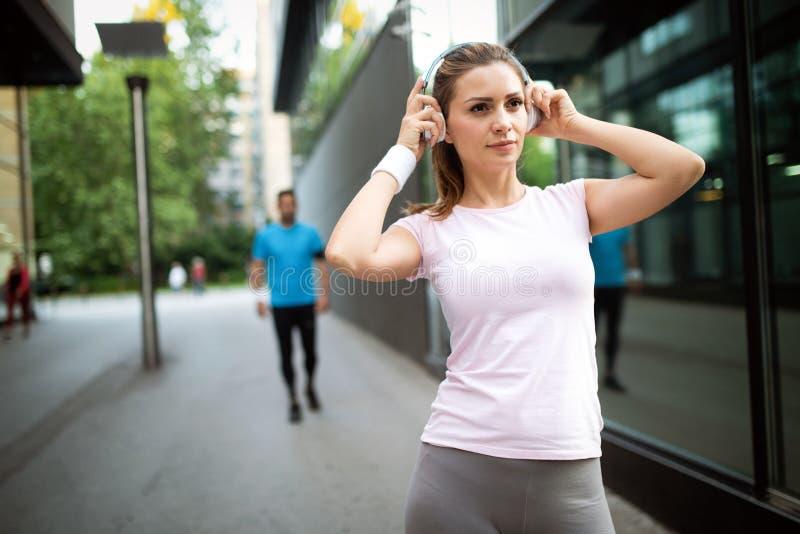 Junge glückliche sportliche Frau, die einen Bruch vom Trainieren macht stockbild