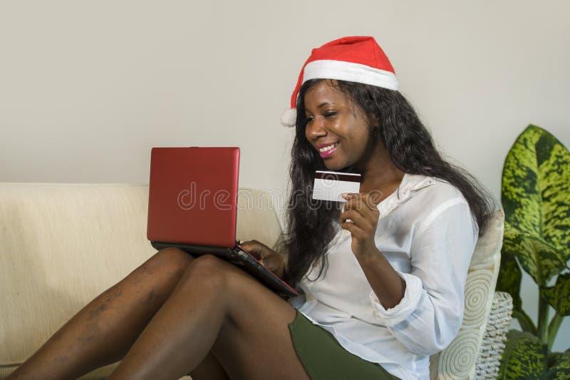 Junge glückliche und attraktive Schwarzafrikaner Amerikanerin in Santa Claus-Hutholdingkreditkartekaufen Weihnachtsgeschenk und i stockfotografie