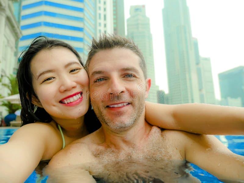 Junge glückliche und attraktive spielerische Paare, die selfie Foto zusammen mit Handy an städtischem Hotelunendlichkeits-Pool Lu stockbild