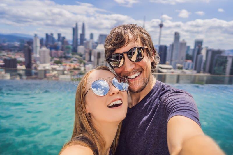 Junge glückliche und attraktive spielerische Paare, die zusammen selfie Foto am städtischen Hotelunendlichkeitsluxuspool machen u lizenzfreie stockfotos