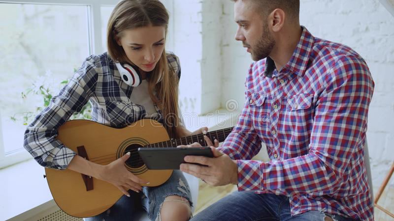 Junge glückliche und liebevolle Paare studieren, um Akustikgitarre unter Verwendung des Tablet-Computers und des Habenspaßes beim lizenzfreies stockbild