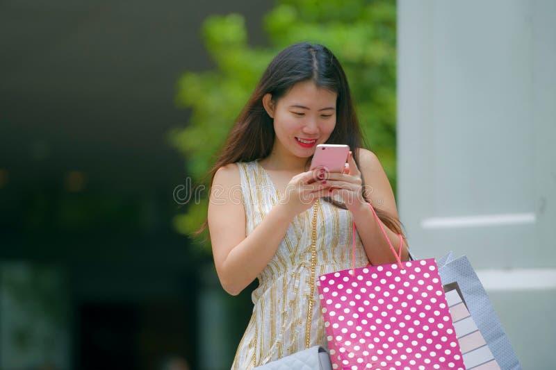 Junge glückliche und schöne asiatische Chinesin, die auf die tragenden Einkaufstaschen der Straße unter Verwendung des Handys onl lizenzfreie stockfotografie