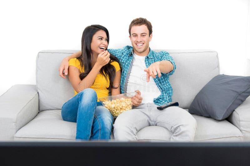 Junge glückliche zwischen verschiedenen Rassen Paare, die auf der Couch fernsehen stockbilder