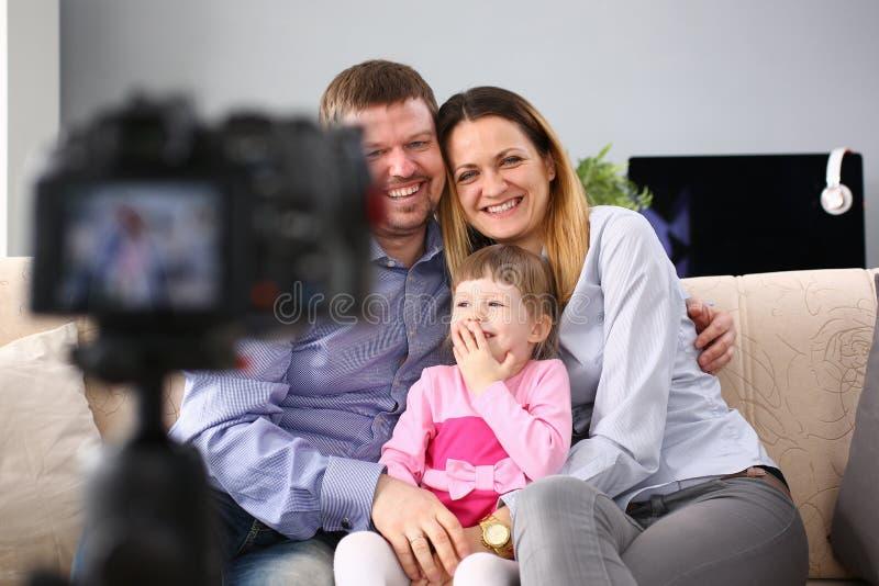 Junge gl?ckliche Familie sitzen auf der Couch, die Fotosessionsportr?t macht lizenzfreies stockfoto