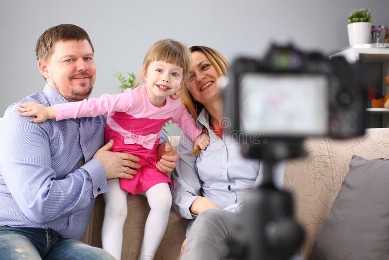 Junge gl?ckliche Familie sitzen auf der Couch, die Fotosessionsportr?t macht lizenzfreie stockfotos
