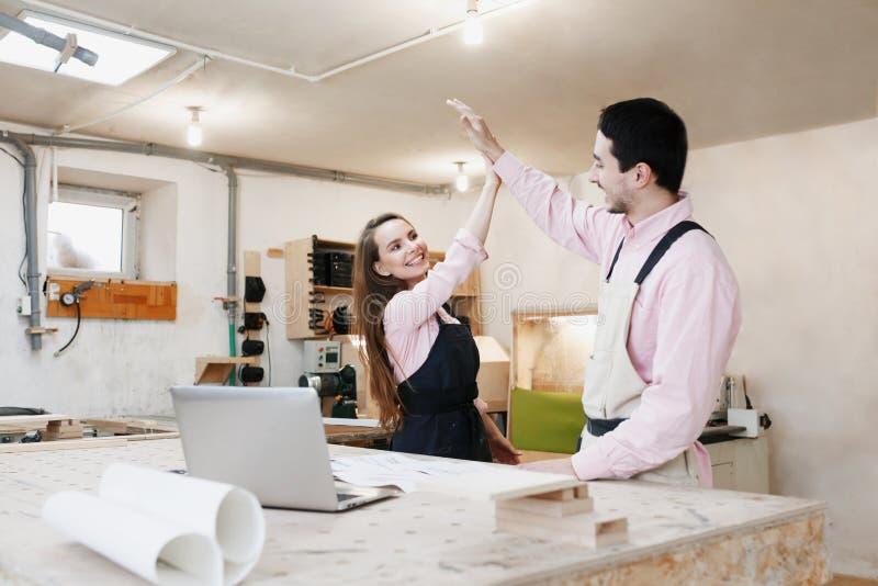 Junge gl?ckliche Familienstellung an einer Werkbank in einer Zimmereiwerkstatt, ein Projekt schreibend Familienunternehmen Startg lizenzfreies stockbild