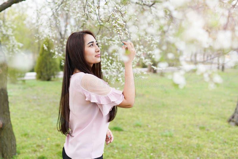 Junge gl?ckliche Frau, die im Fr?hjahr Blumengarten geht Kopieren Sie Platz Gr?ner Hintergrund lizenzfreie stockfotos