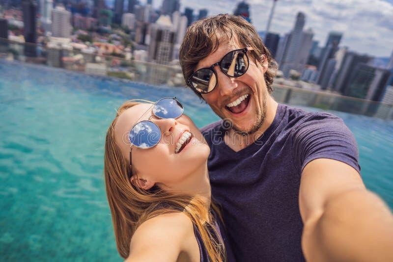 Junge gl?ckliche und attraktive spielerische Paare, die zusammen selfie Foto am st?dtischen Hotelunendlichkeitsluxuspool machen u lizenzfreie stockbilder
