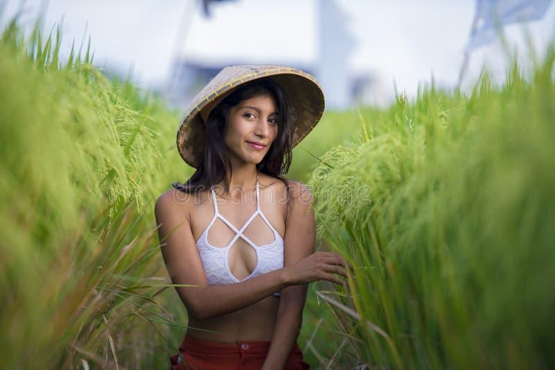 Junge gl?ckliche und sch?ne lateinische Frau, die mit dem traditionellen asiatischen Landwirthut l?chelt spielt, den Spa? habend, lizenzfreies stockfoto